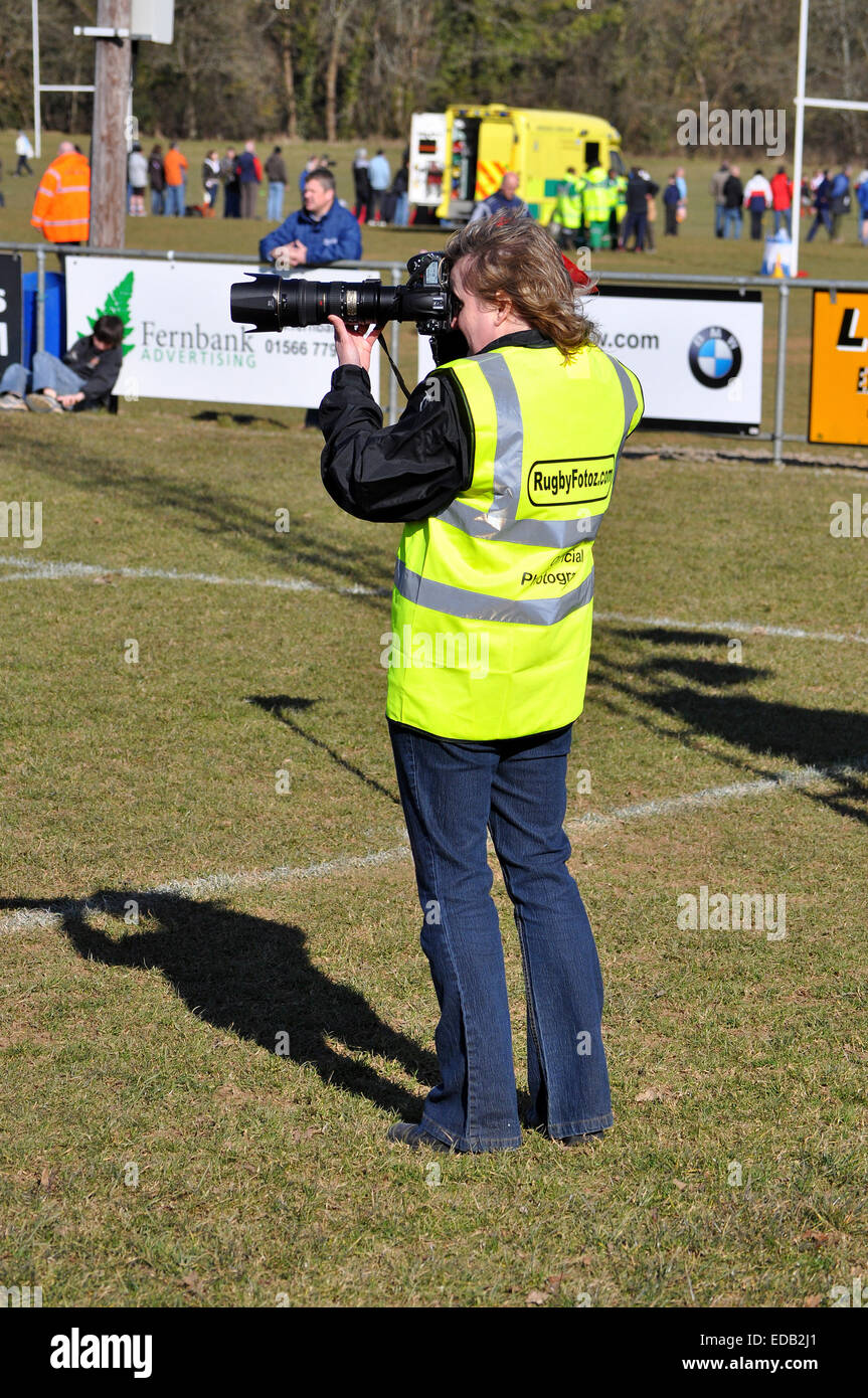 A professional photographer at a sports game - Stock Image