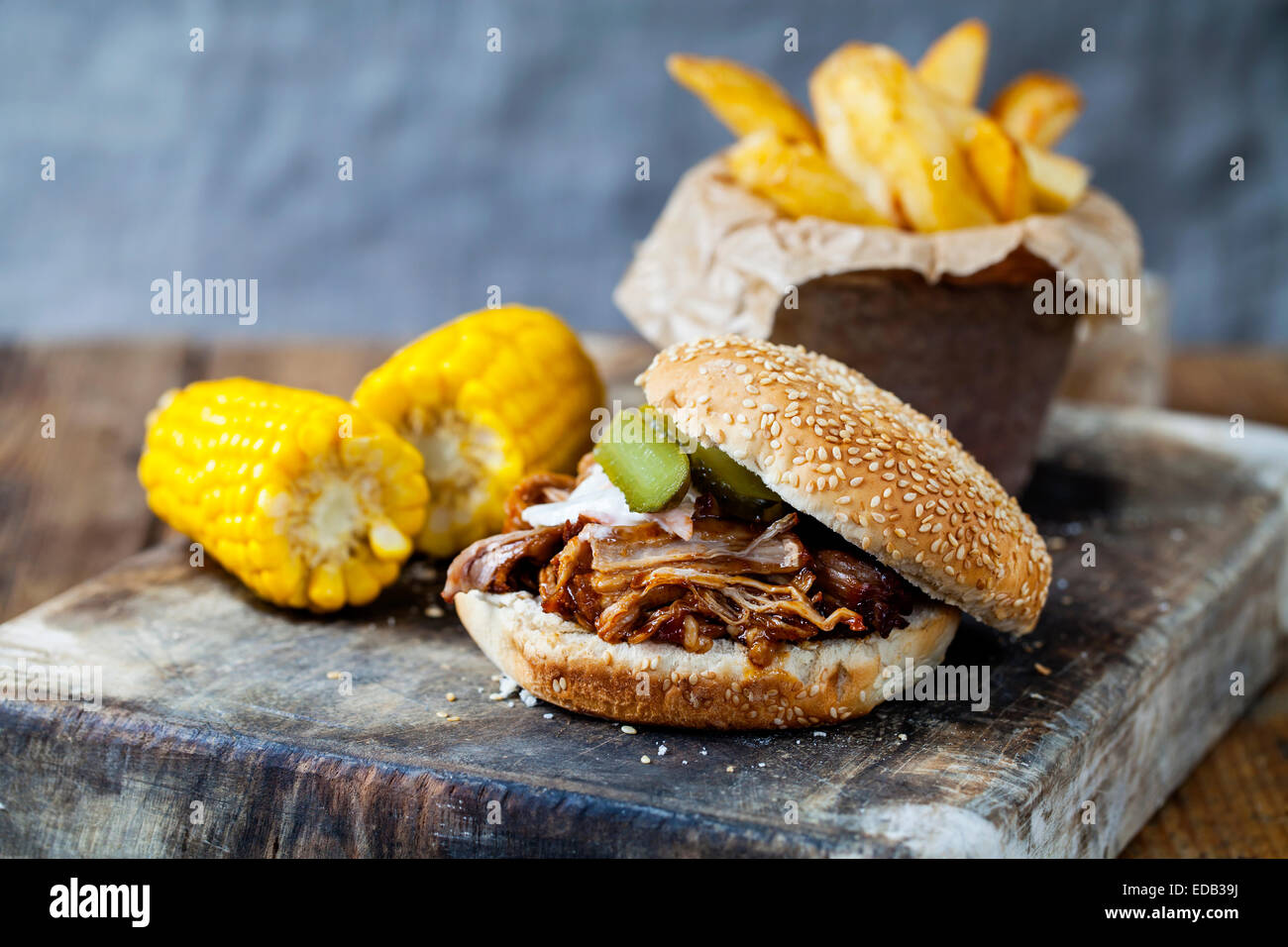 Burger with pulled pork, sweetcorn and chips - Stock Image