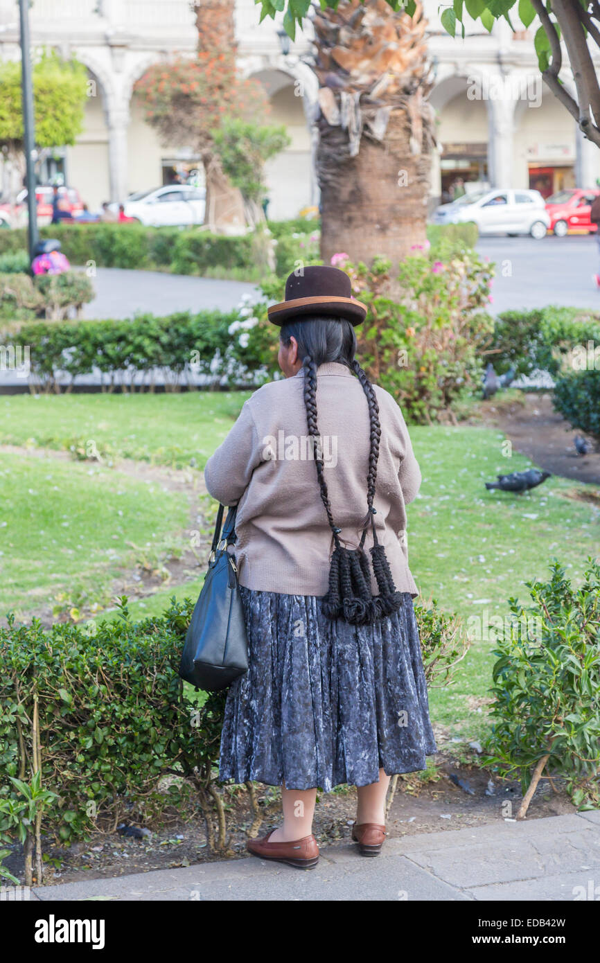 Native Peruvian old woman in traditional local dress and hat with very long plaits with purse, in Plaza de Armas, - Stock Image