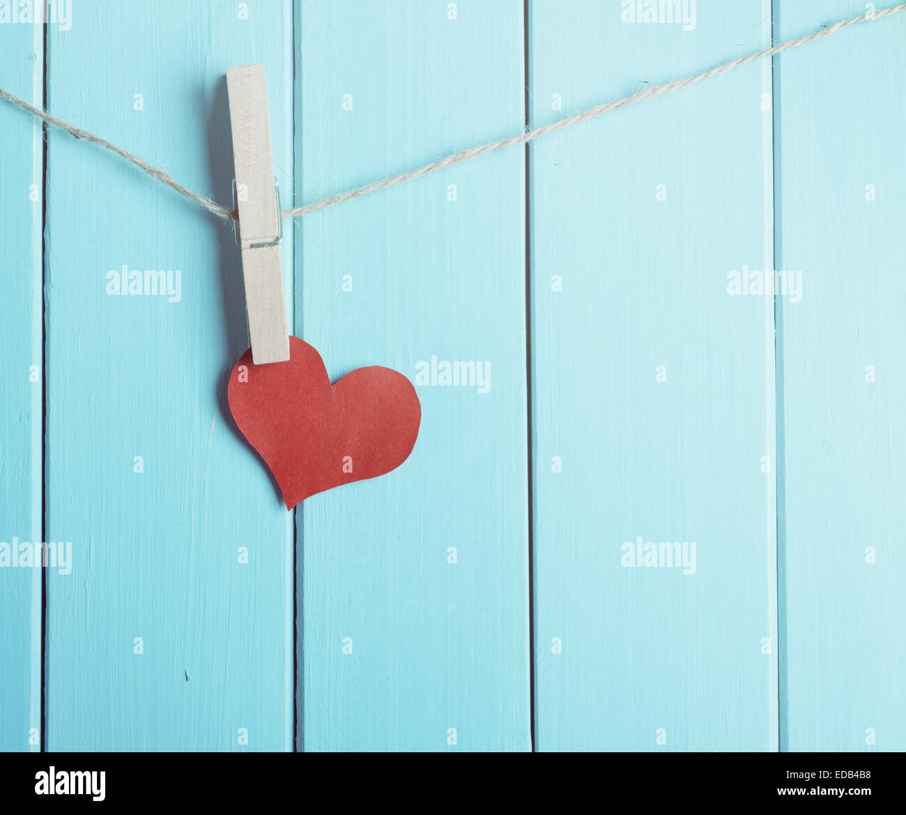 red heart made of paper with clothespin hanging on a rope and wooden blue  planks background with space for text - Stock Image