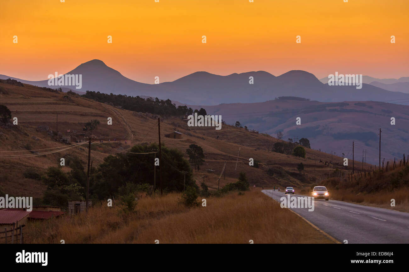 SWAZILAND, AFRICA - Wood fire smoke creates orange sunset over mountain landscape, as cars drive on highway. - Stock Image