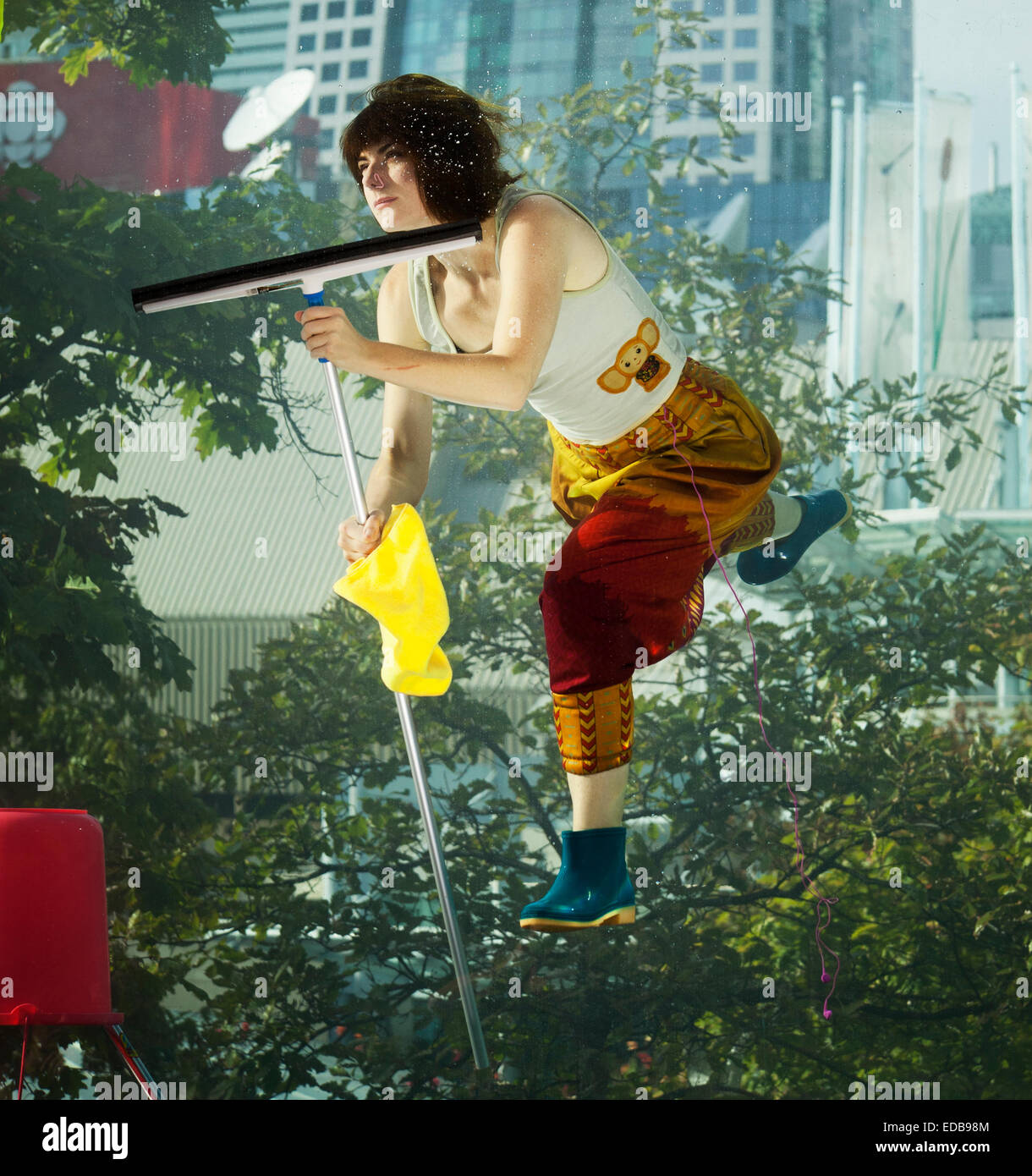 Street performance. Girl washing windows underwater in glass tank, Toronto, Canada - Stock Image