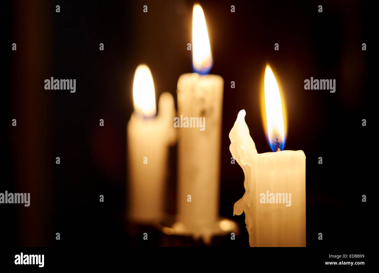 Flame of burning candle by night - Stock Image