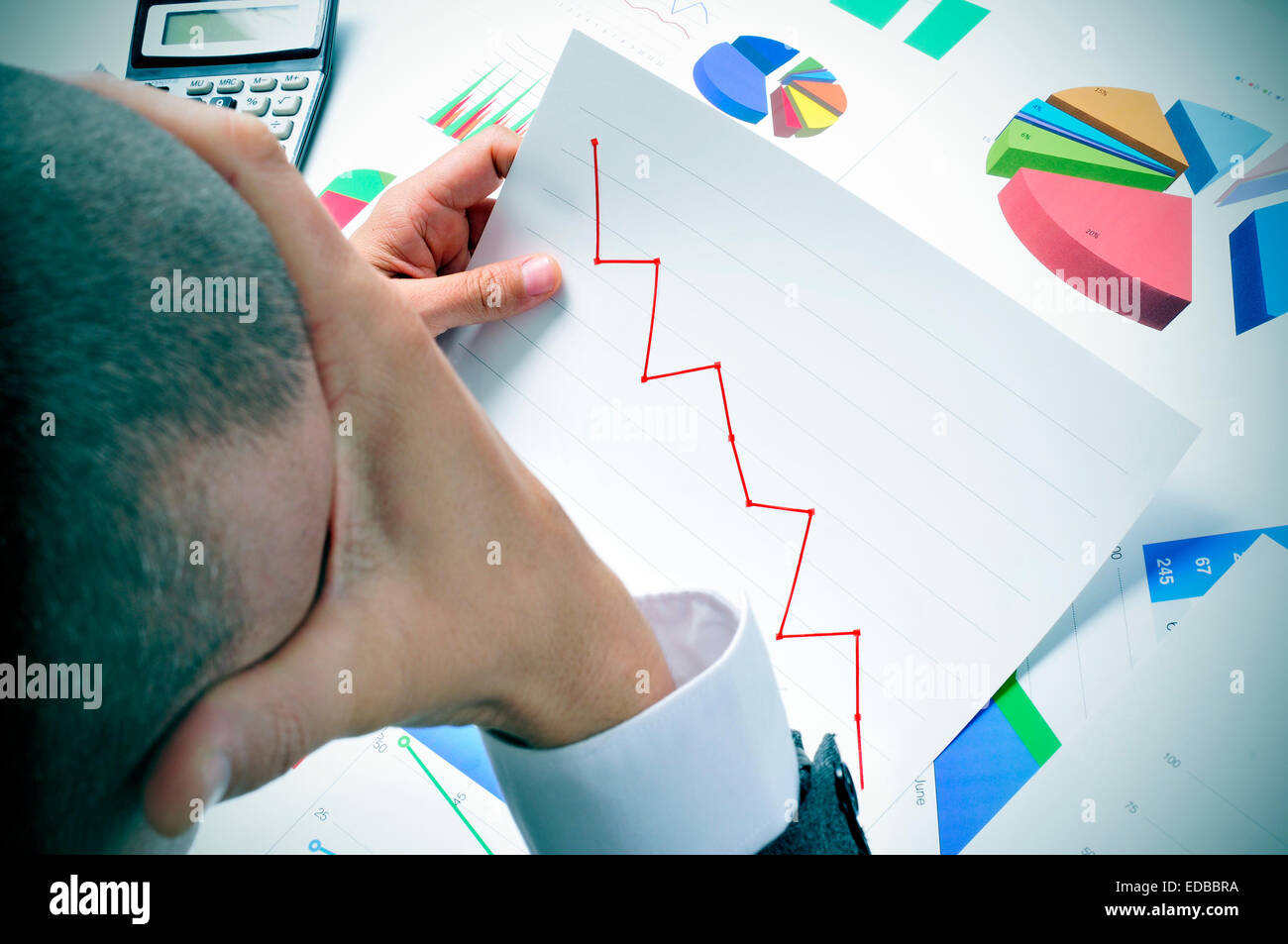 businessman in his office desk full of graphs and charts observing worried a chart with a downward trend - Stock Image