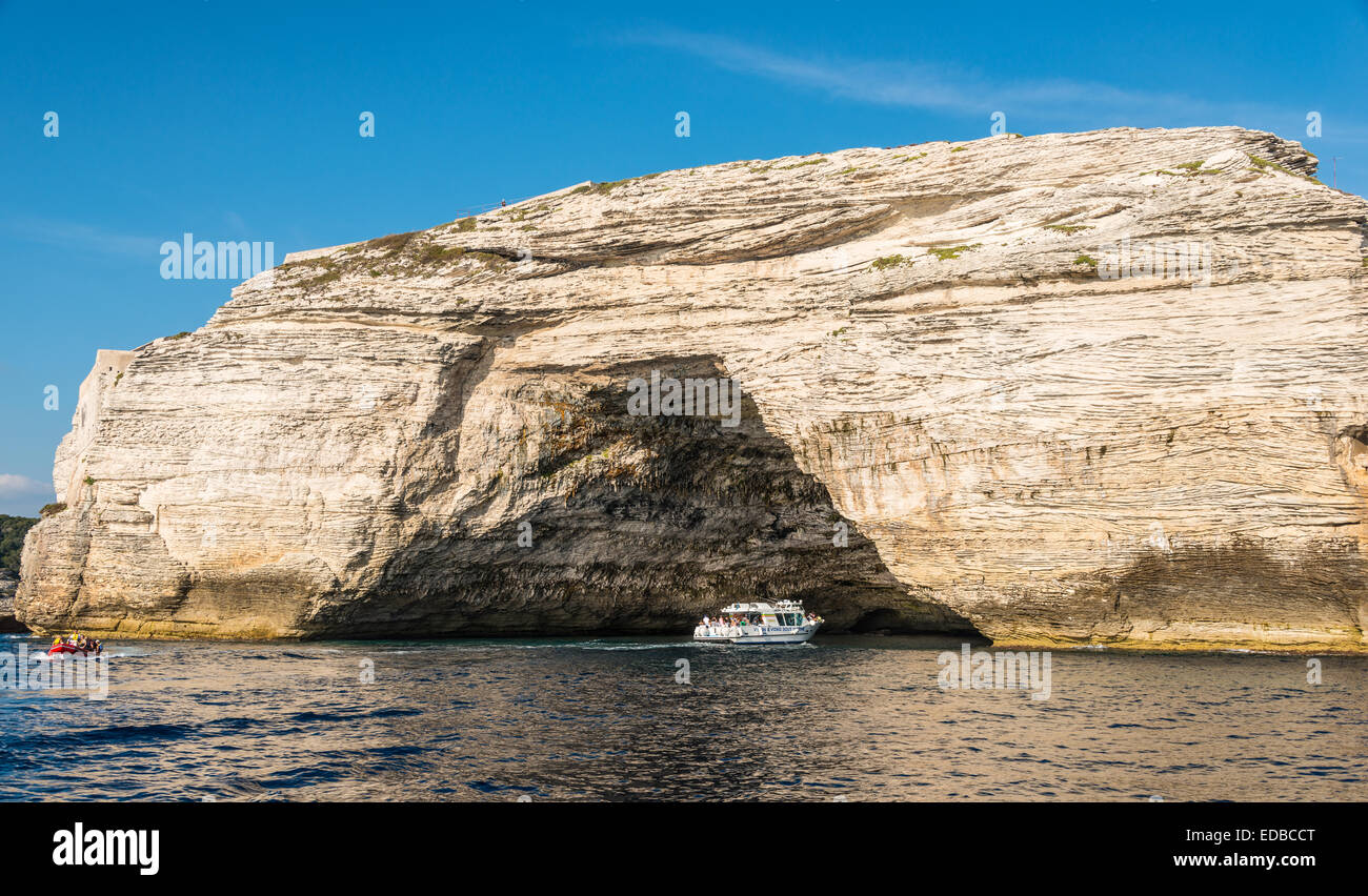 Excursion boat visiting a cave in the chalk cliffs, Bonifacio, Corsica, France - Stock Image