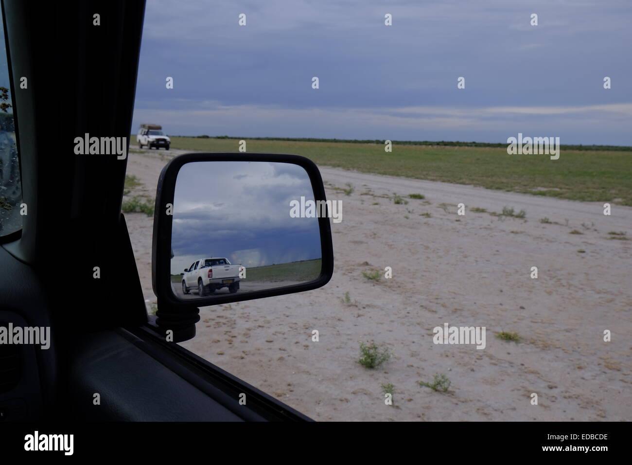 Four wheel drive game viewing vehicles in a gathering rainstorm Central Kalahari National Park Botswana. - Stock Image