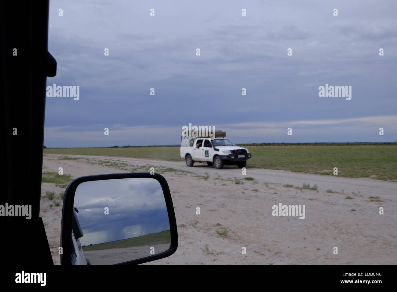 Two 4 wheel drive vehicles game viewing in the Central Kalahari Botswana. - Stock Image