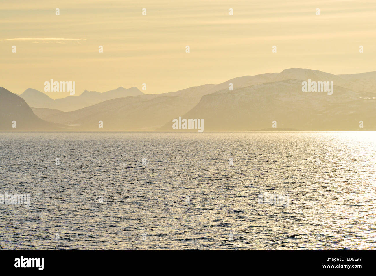 Glistening water and the mountains of Hinnøya in the yellow morning light, Toppsund, Troms, Norway - Stock Image