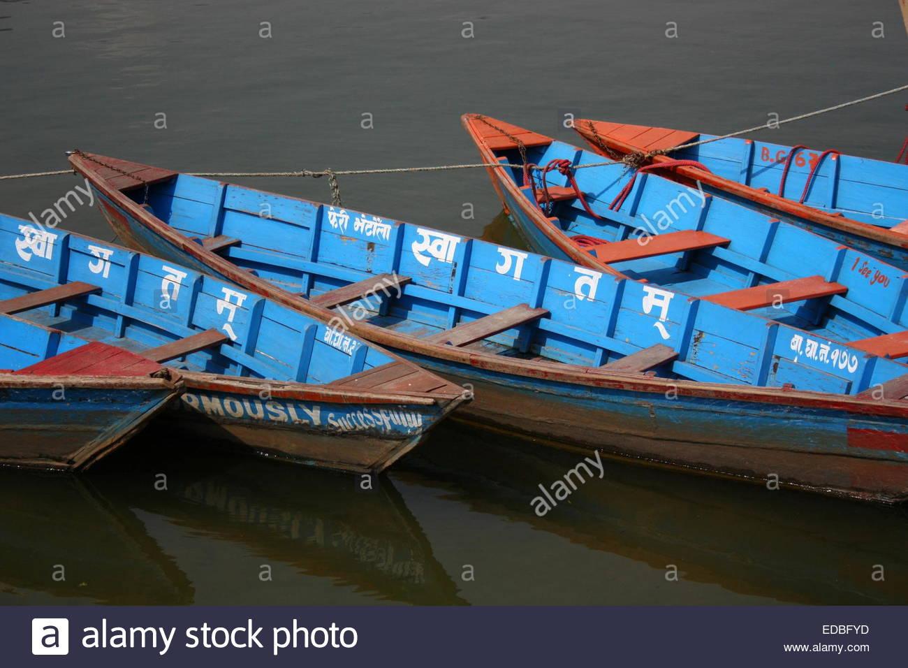 Blue rowing boats on Phewa Lake, Pokhara, Nepal - Stock Image