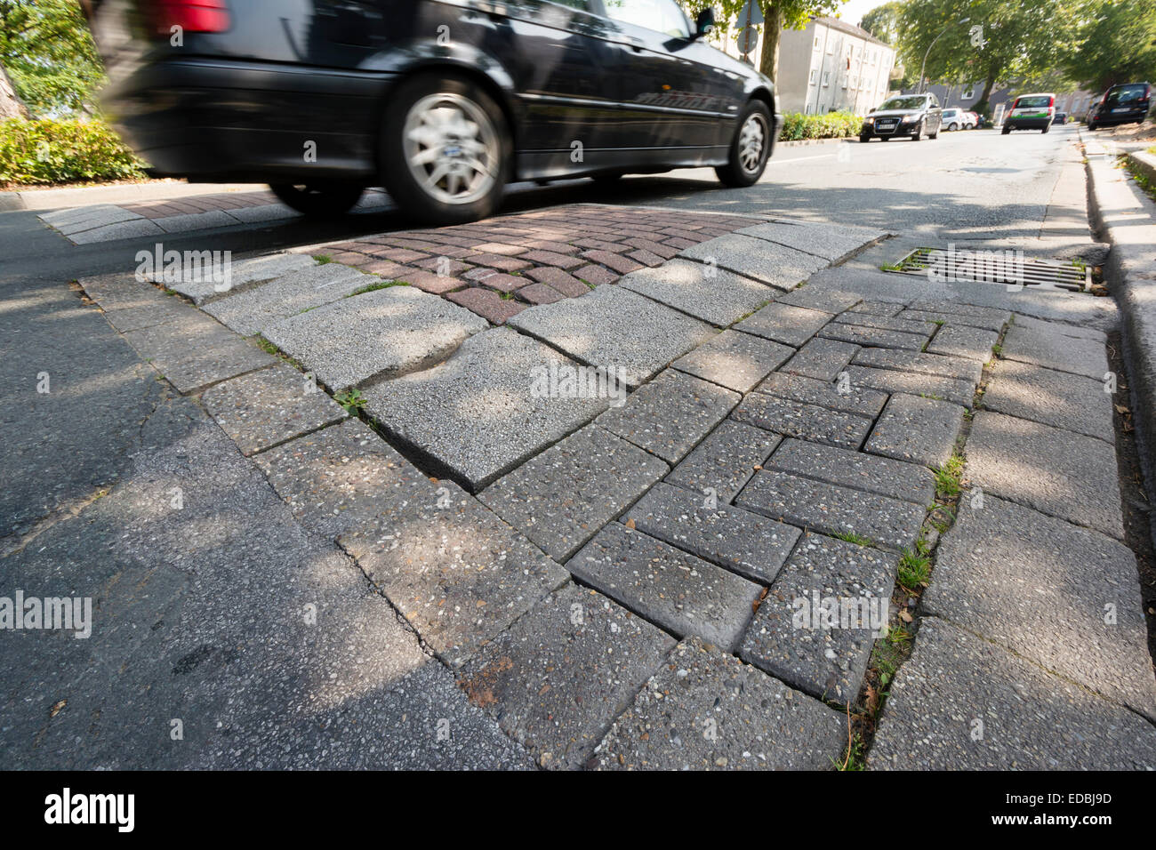 Cars drive on a street in the Ruhr area that is in bad condition and like many others in need of redevelopment. - Stock Image
