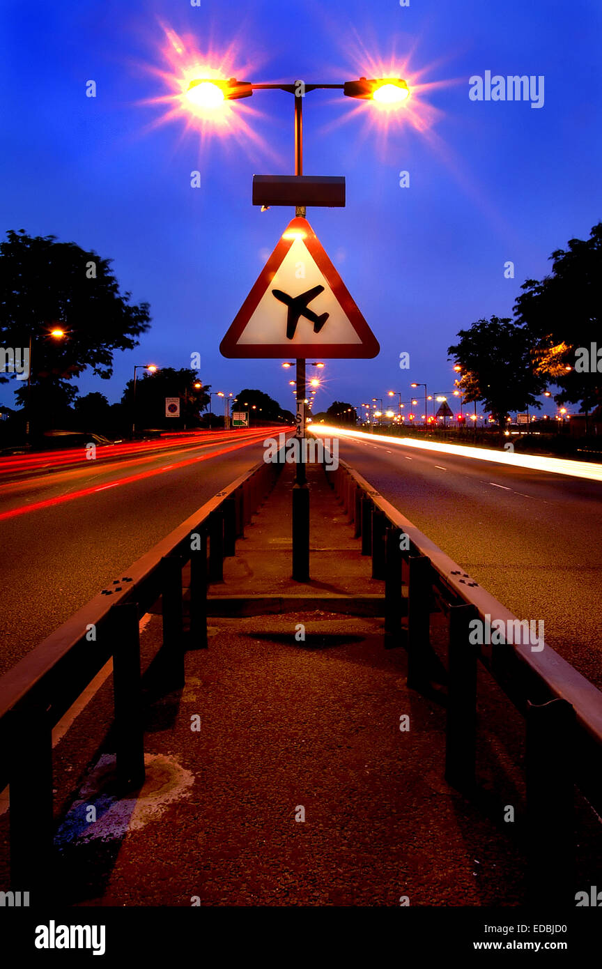 A long exposure of a dual carriageway close to Heathrow Airport and a road sign warning of low flying aircraft. - Stock Image
