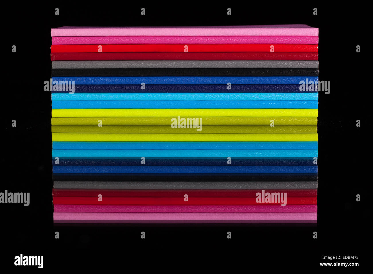 Twelve different color diaries on a black glass desk - Stock Image