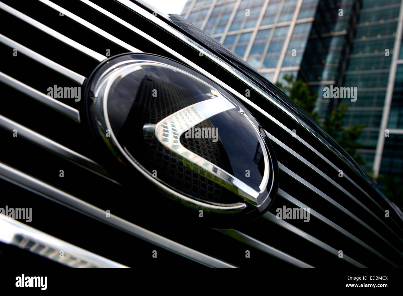 Picture shows a highly polished Lexus in Canary Wharf, London. With the emblem reflecting the One Canada Square - Stock Image