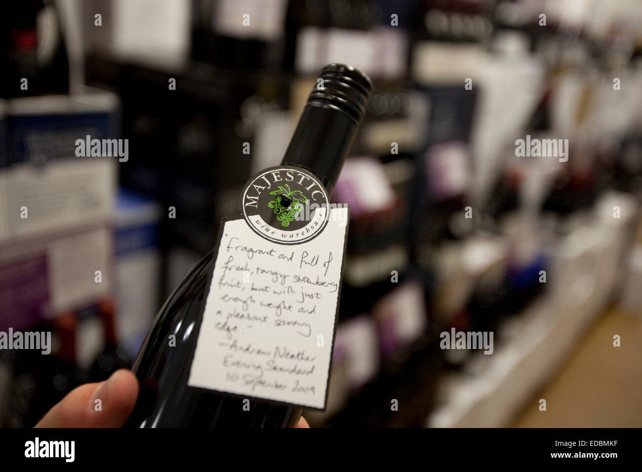 A customer reading the wine description of his selected bottle. - Stock Image