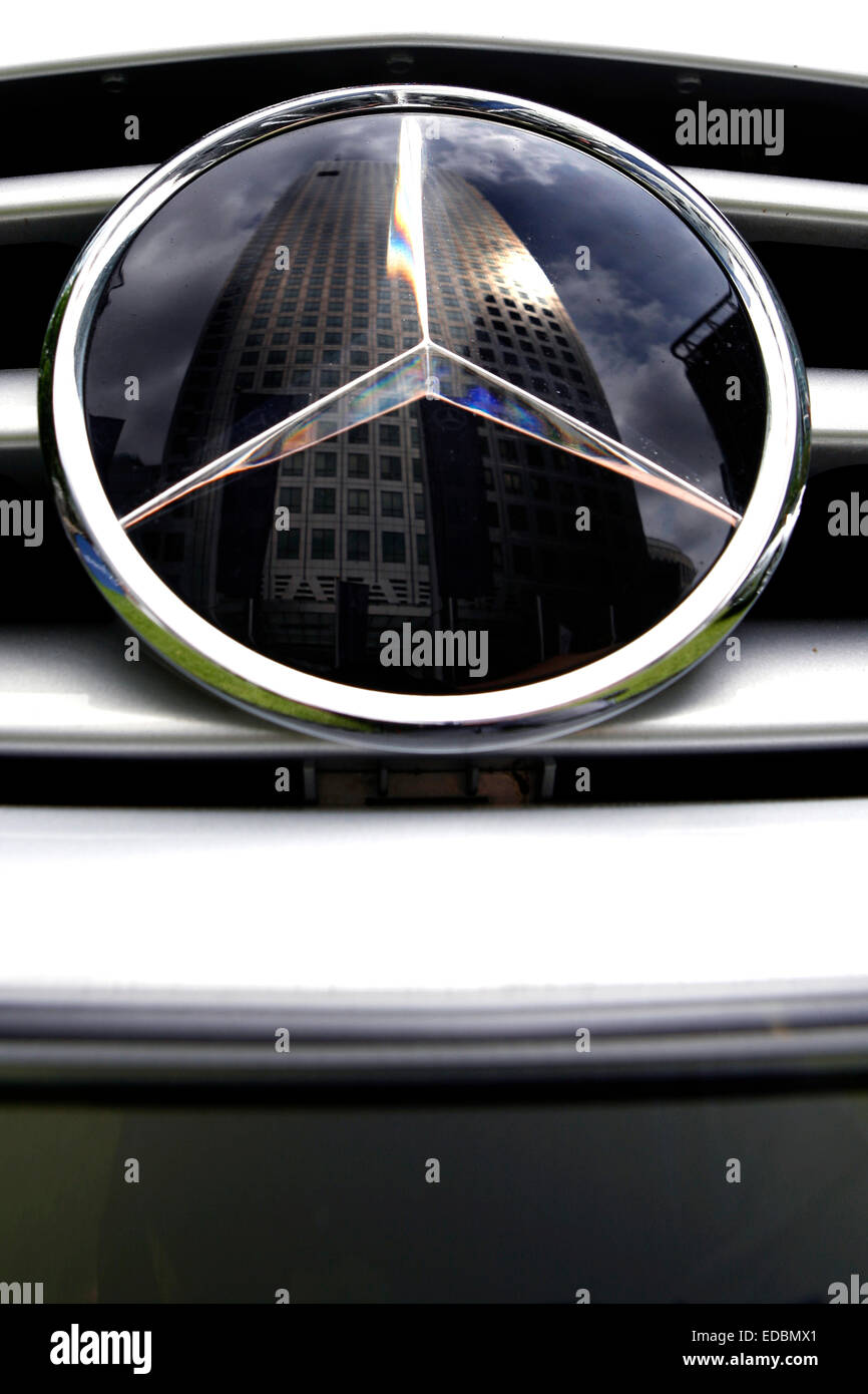 Picture shows a highly polished Mercedes in Canary Wharf, London. The badge reflects the One Canada Square building. - Stock Image