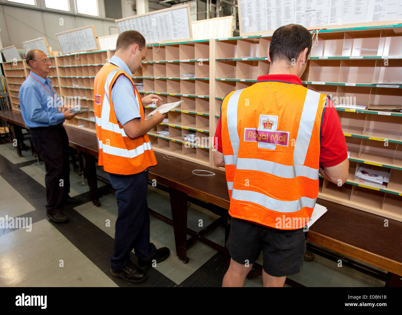 Postal workers sort letters at a Royal Mail delivery office, Royston. - Stock Image