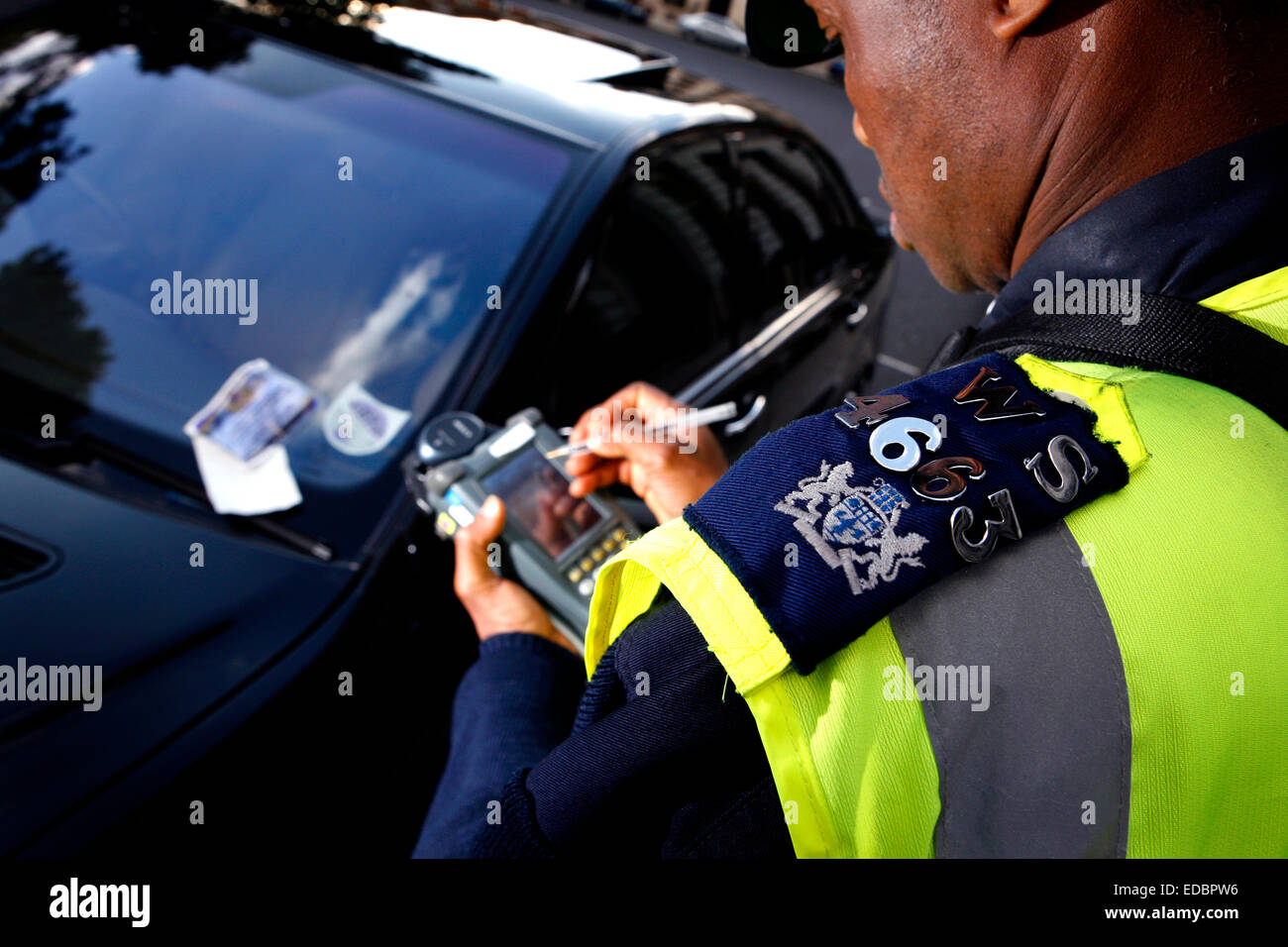 A traffic warden issues a parking ticket - Stock Image