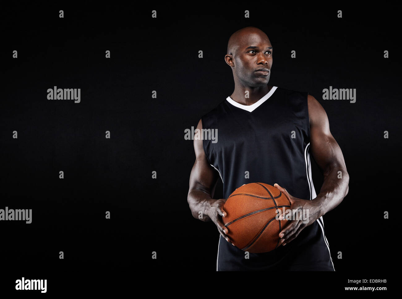 Image of fit young Afro American athlete holding a basketball looking away with copy space. Muscular basketball - Stock Image