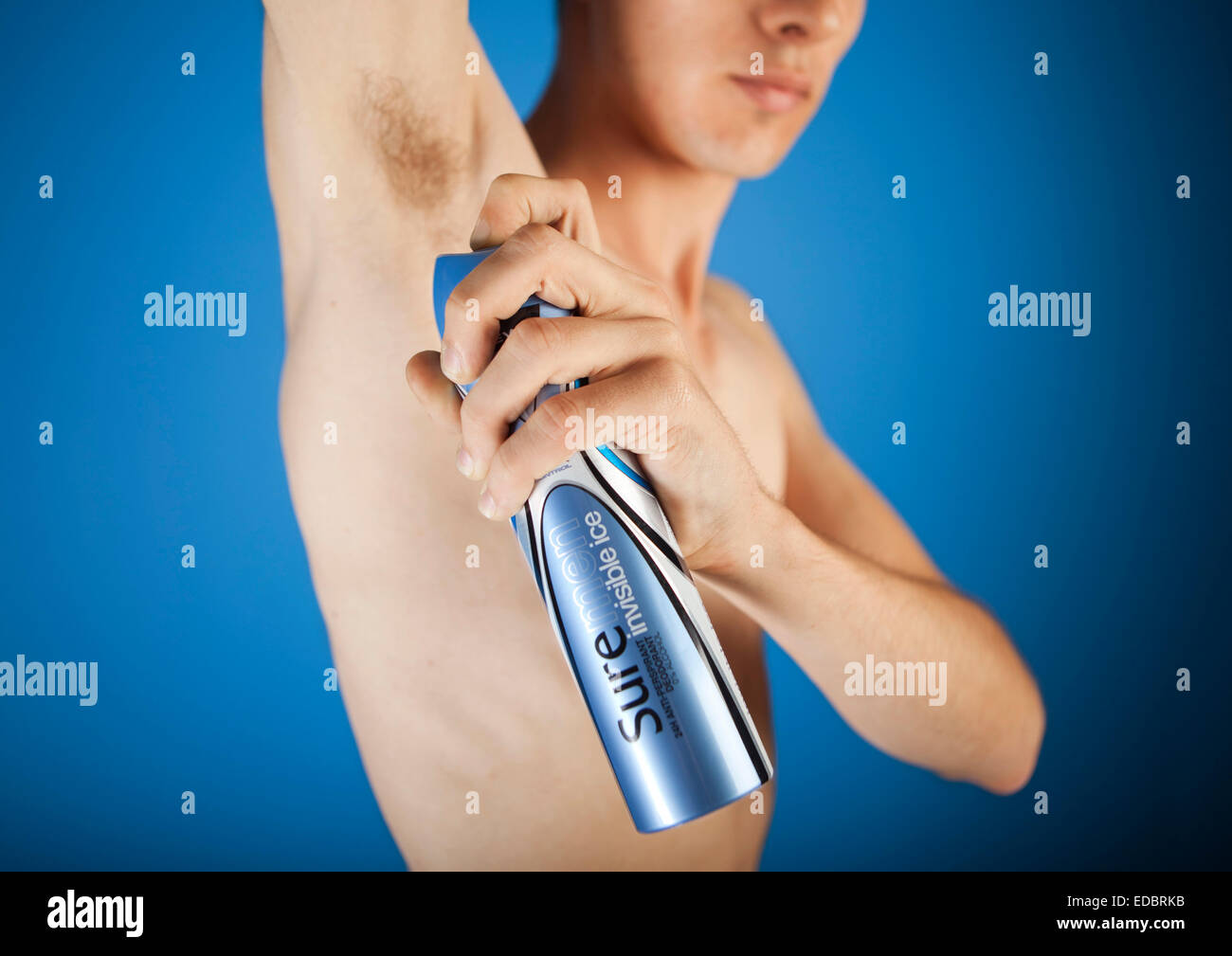 Illustrative image of a man using Sure for Men Invisible deodorant. A Unilever brand. - Stock Image