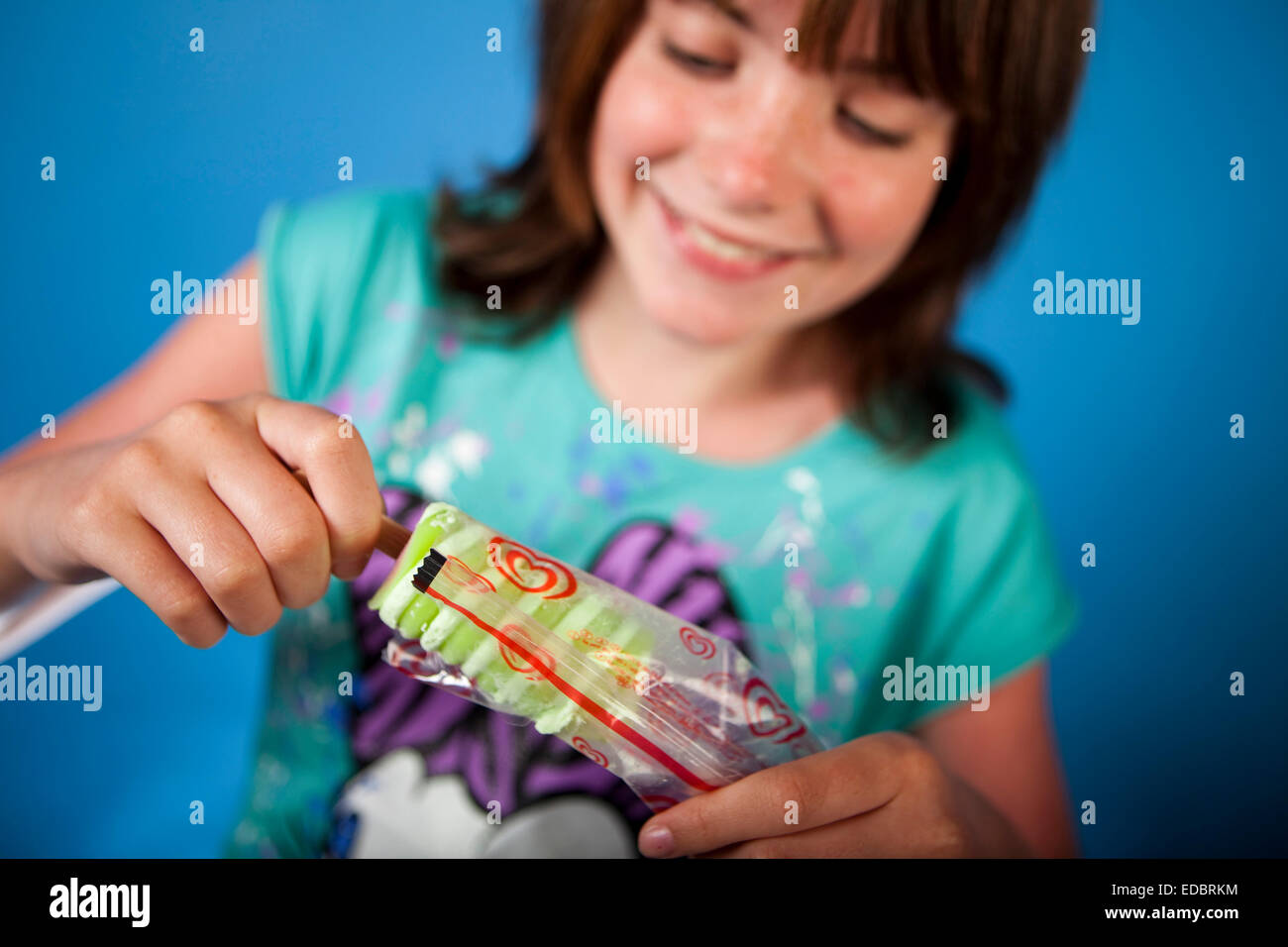 A young girl enjoys a Walls Twister ice-lolly, a Unilever brand. - Stock Image