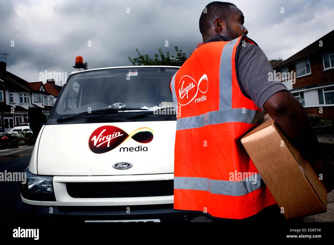 A Virgin Media employee delivering a digital tv reciever. - Stock Image