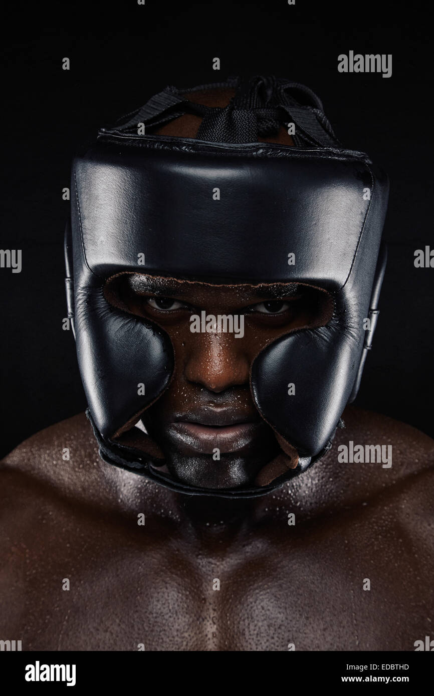 Close-up portrait of strong African man wearing head protector against black background. Tough male  boxer in boxing - Stock Image