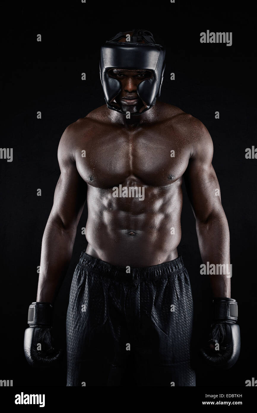 Portrait of African American boxer wearing protective gear standing on black background. Muscular young man in boxing - Stock Image