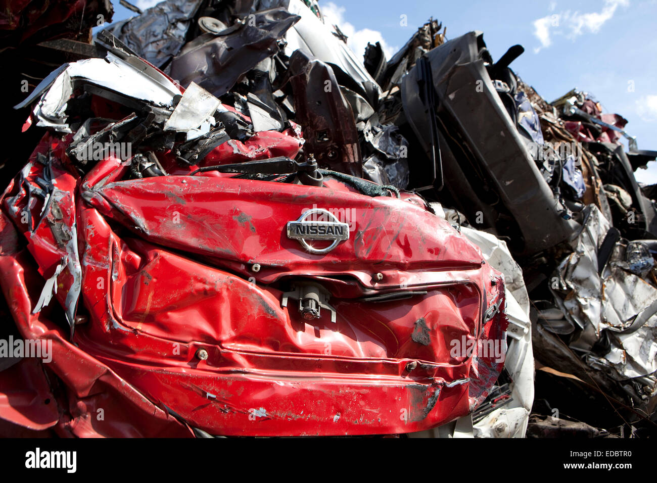 A Nissan car logo is visible amongst a pile of crushed cars. - Stock Image