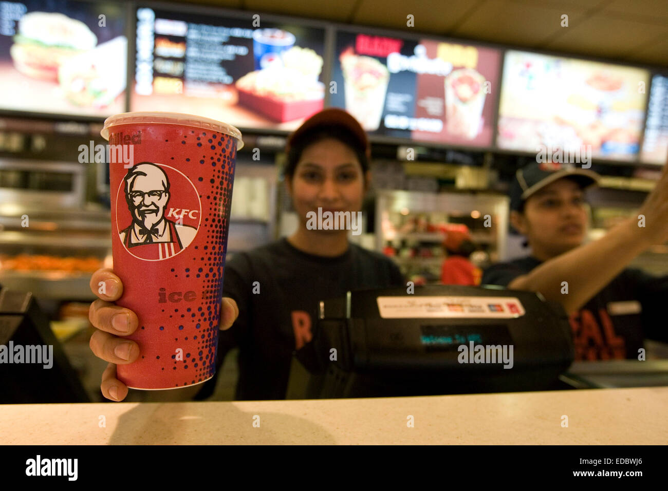 A KFC employee serves a thirsty customer in the restaurant on Oxford Street, Central London - Stock Image