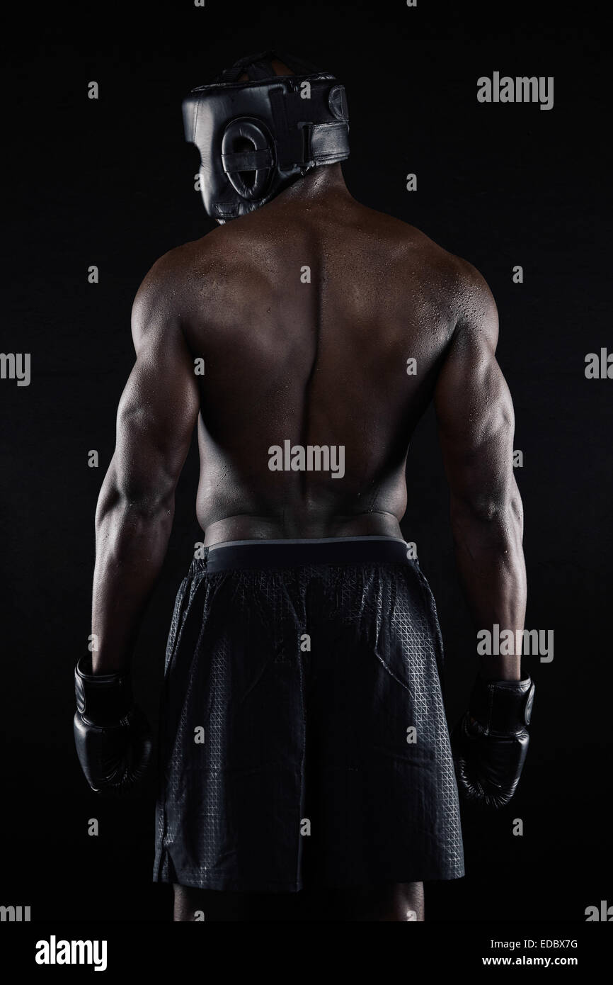 Back of strong young male boxer on black background. Young African male in boxing gear. - Stock Image
