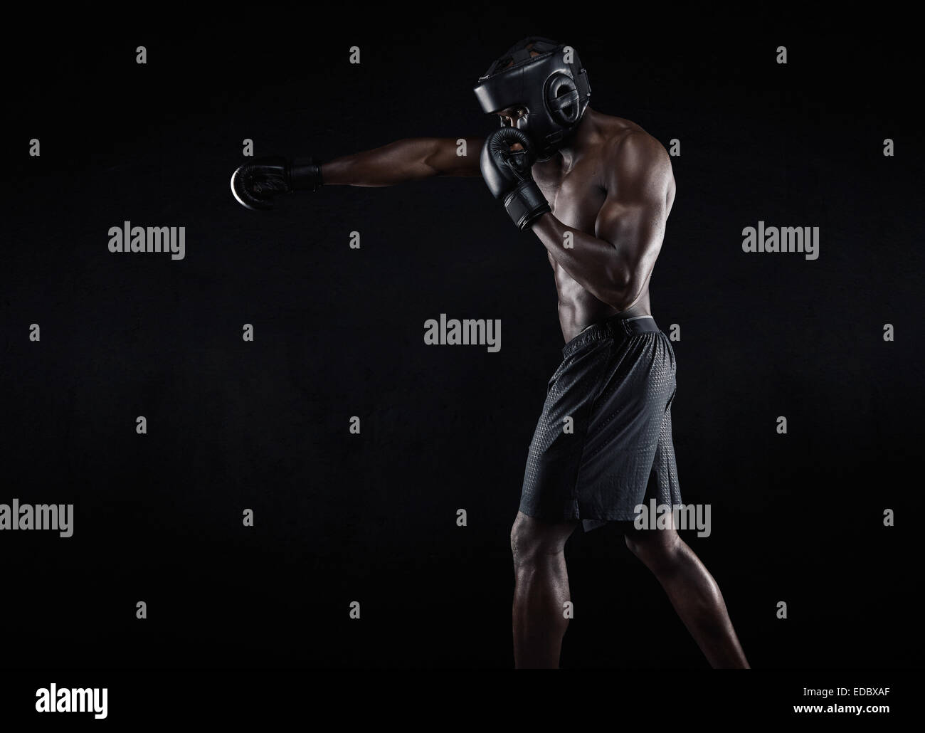 Side view of muscular man boxing on black background. Afro American young male boxer practicing shadow boxing. - Stock Image