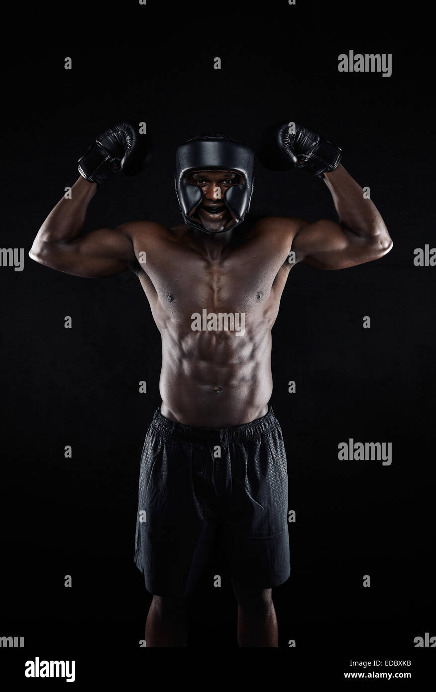 Portrait of happy young African boxing winner on black background. Muscular male boxer celebrating his win with - Stock Image
