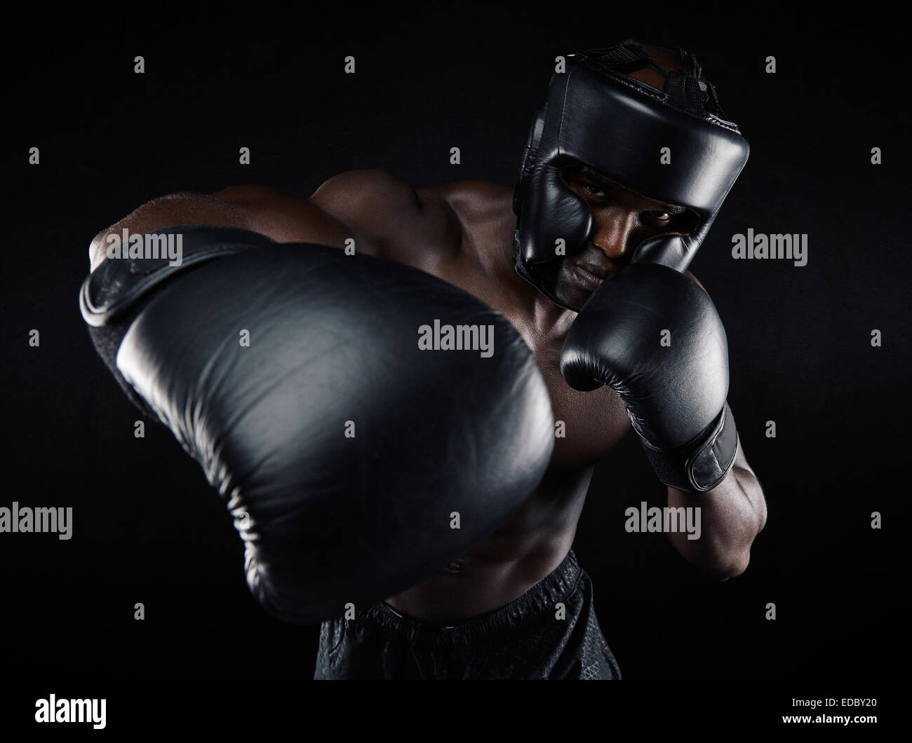 Portrait of young male practicing boxing against black background. African Male boxer throwing a punch in front. - Stock Image