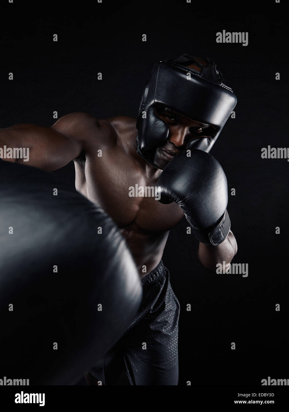Portrait of a young man boxer throwing a punch at camera while practicing on black background. Male athlete wearing - Stock Image