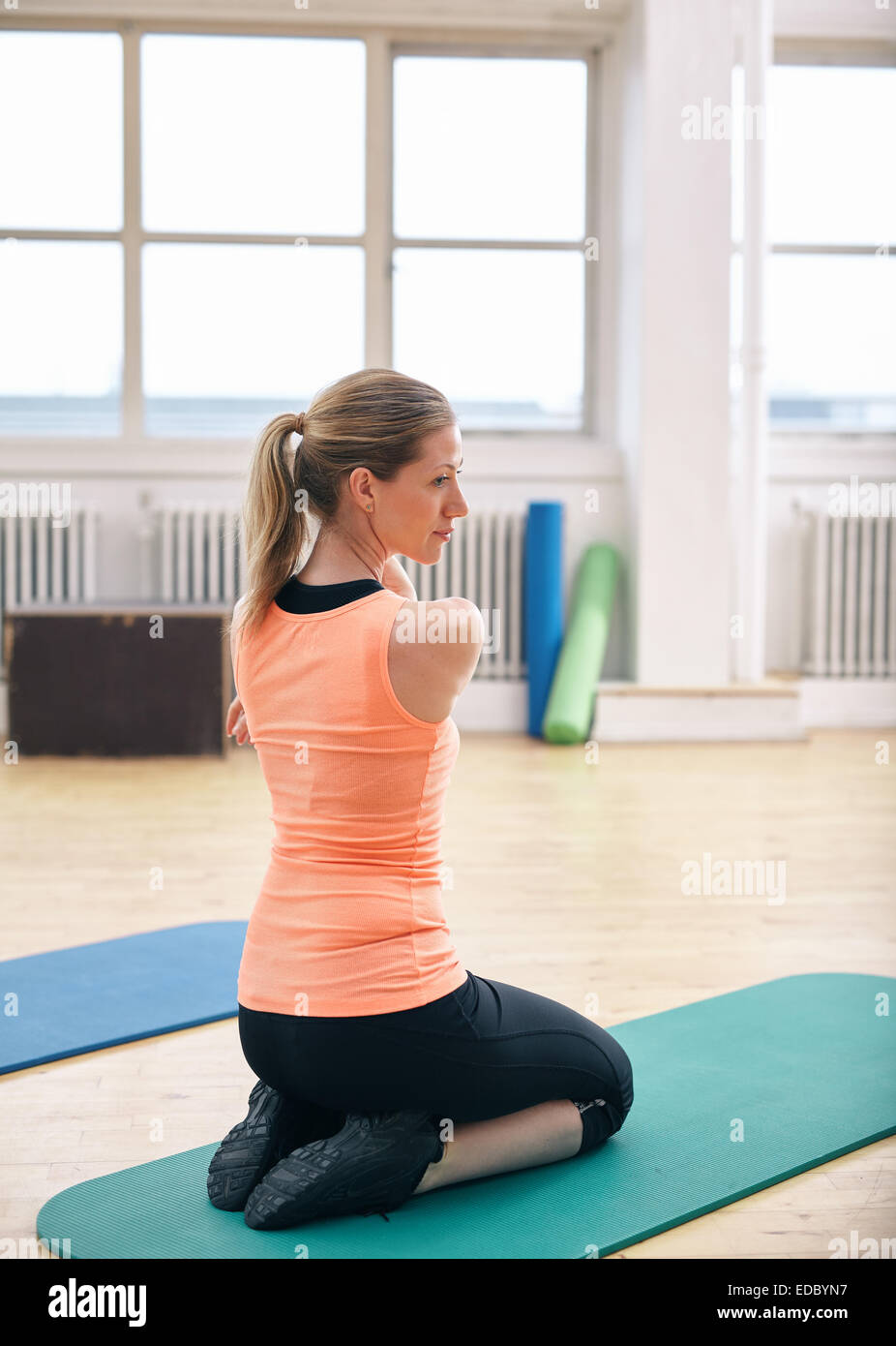 Woman sitting on fitness mat doing stretching exercises at gym. Fit Caucasian woman working out at health club. - Stock Image