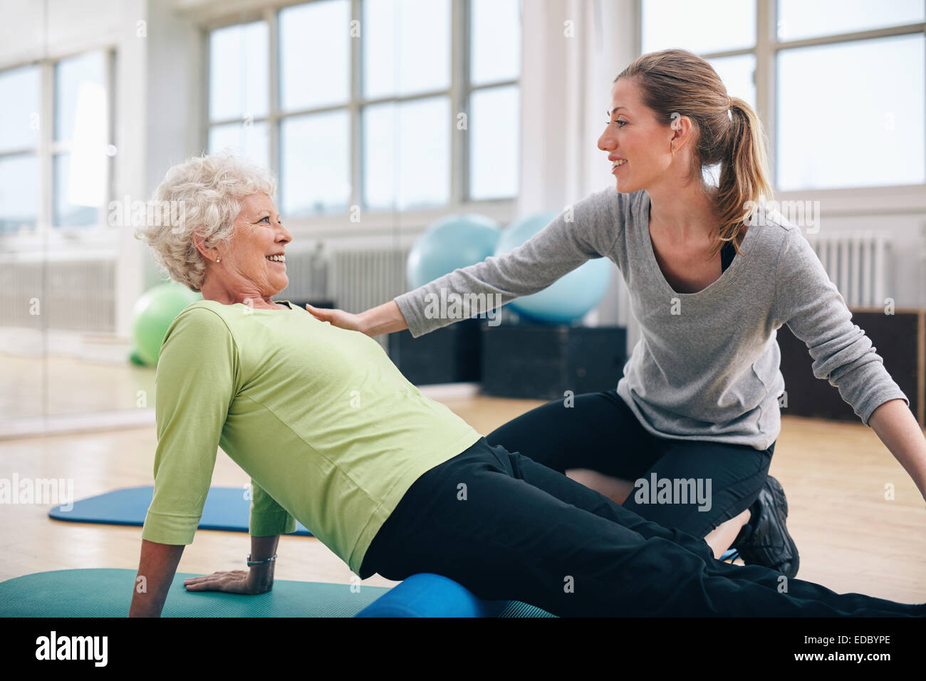 Physical therapist working with a senior woman at rehab. Female trainer helping senior woman doing exercise on foam - Stock Image