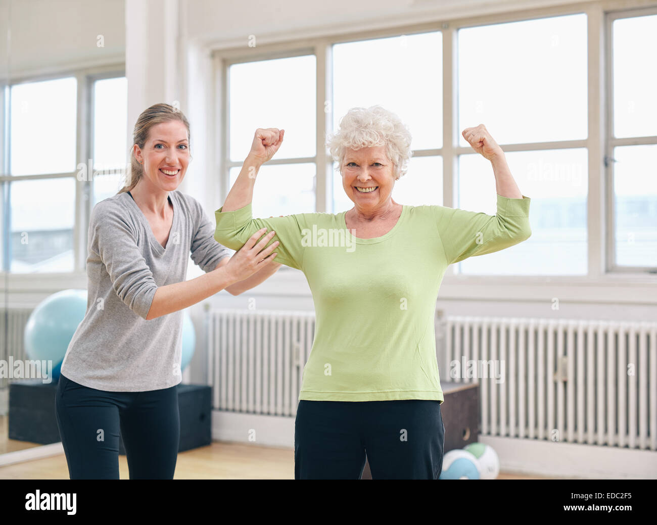 Portrait of a fit old woman flexing her arms and showing her muscles with personal trainer at gym Stock Photo