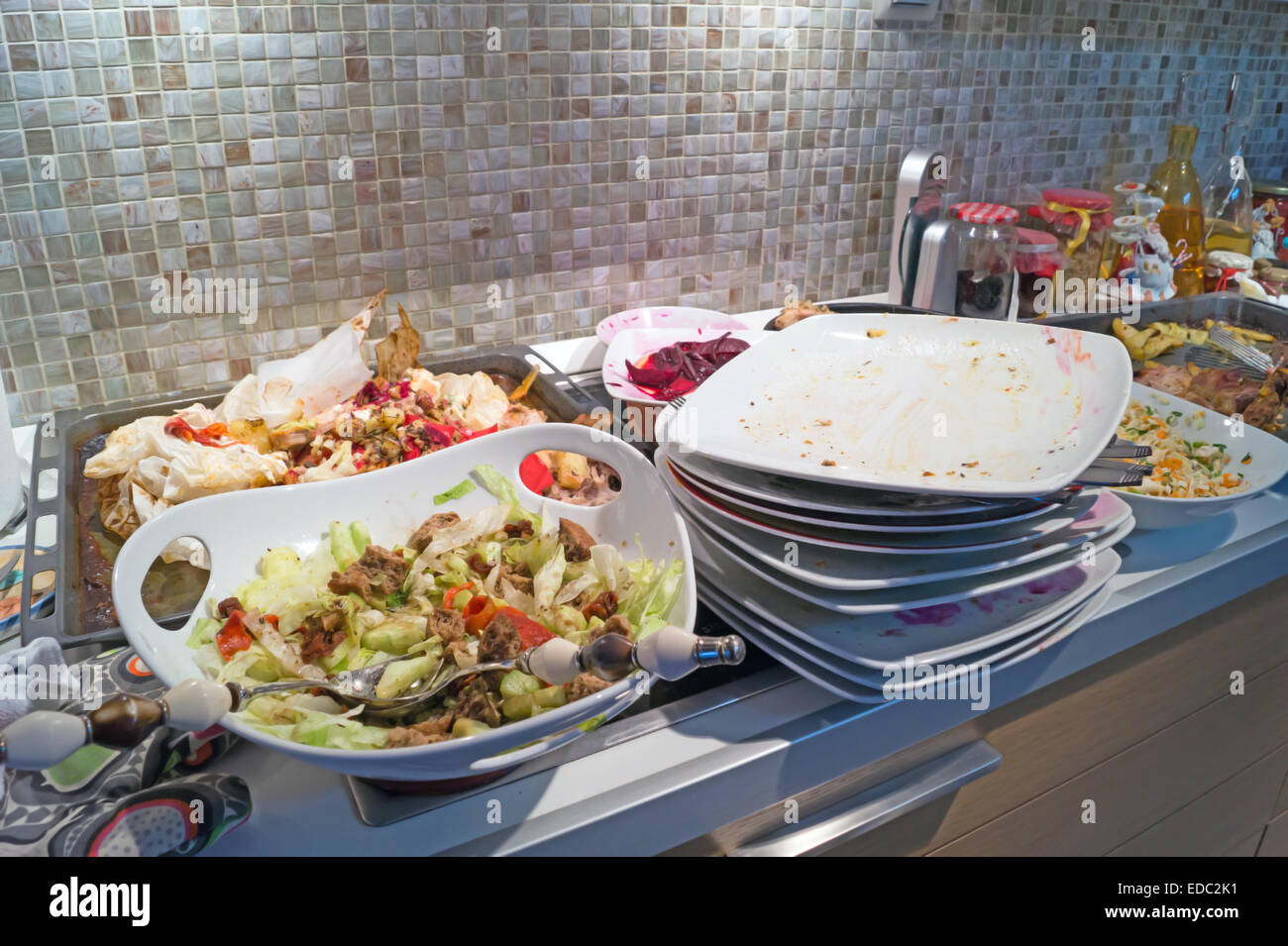 A mass of dirty, filthy dishes with food scraps waiting to be washed - Stock Image