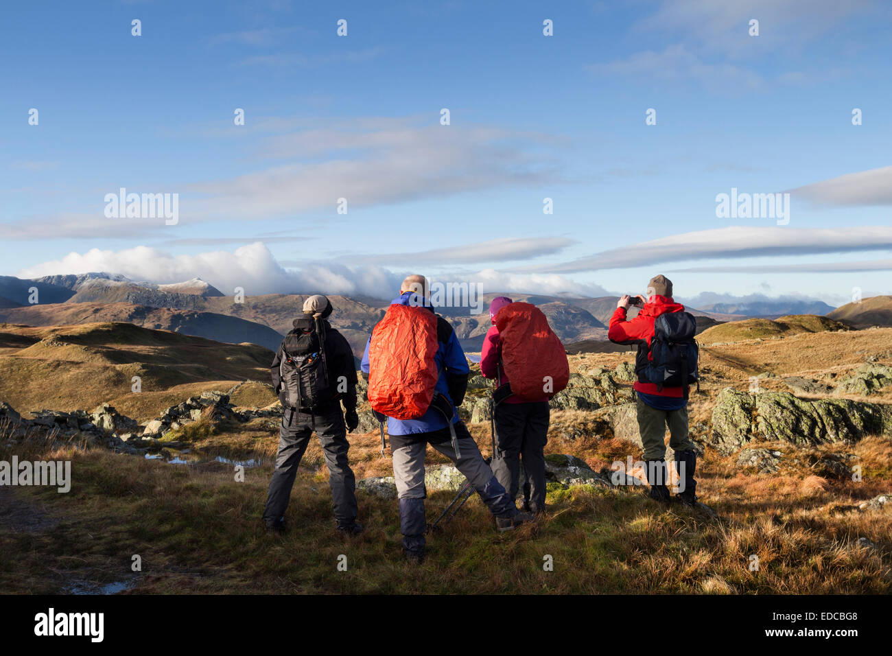 Four Hill Walkers on Satura Crag Enjoying the Spectacle of Cloud Spilling Over Helvellyn and the Dodds Lake District - Stock Image