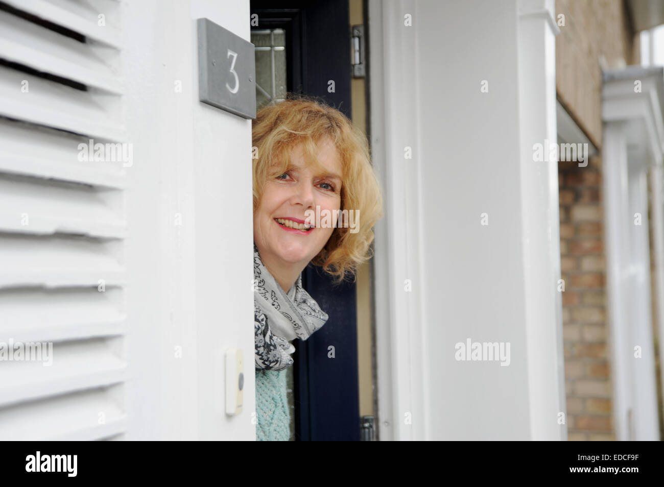 Woman looking out of her front door to greet visitors Stock Photo