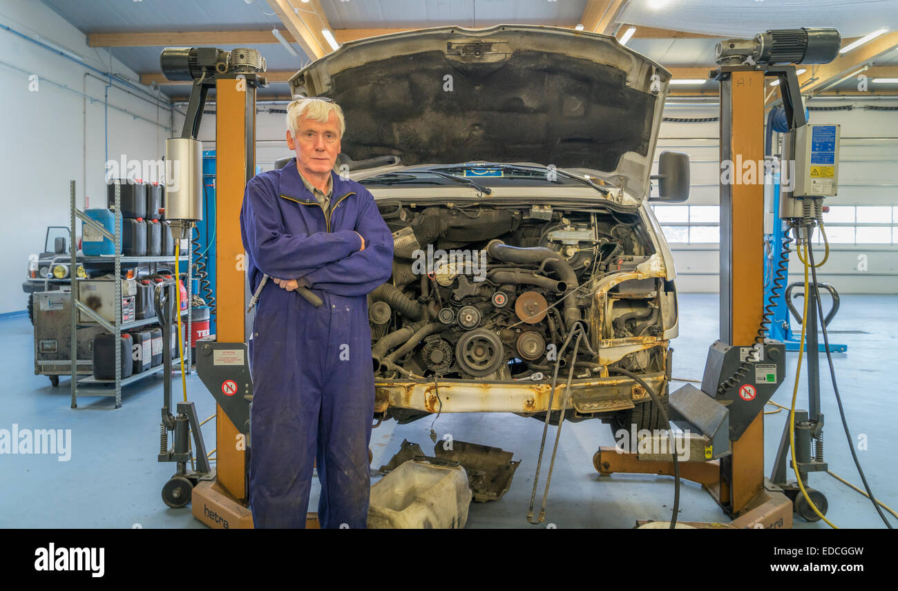 Auto mechanic working on a car inside a garage, Reykjavik, Iceland - Stock Image