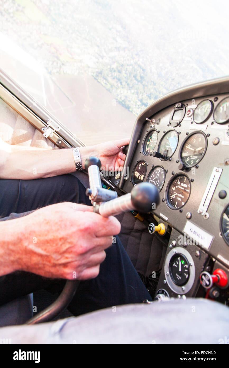 Man flying using joystick turning Bolkowl Junior Bo 208 G-BOKW 'C' model plane aircraft airplane - Stock Image