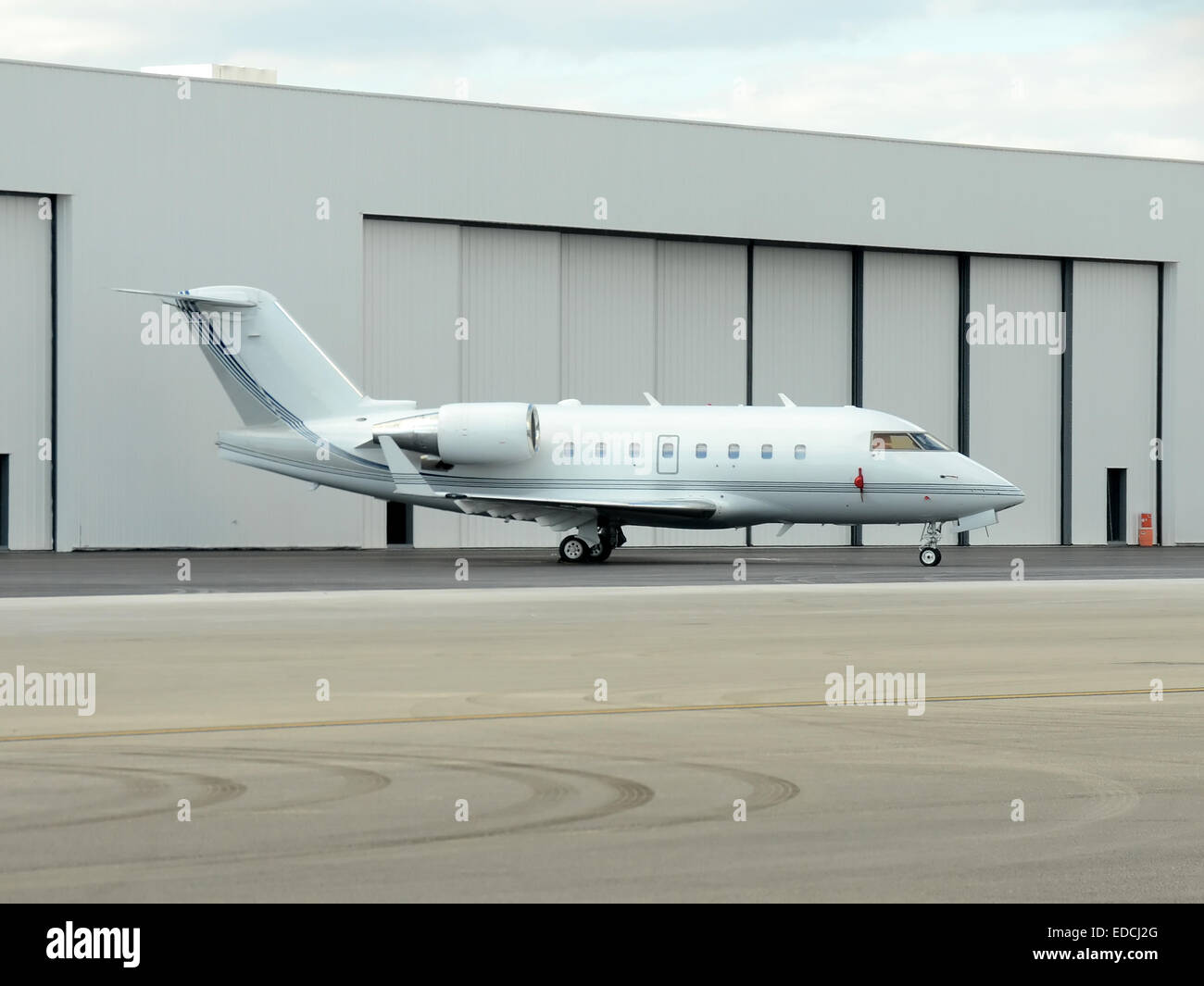 Modern corporate jet airplane in front of hangar Stock Photo