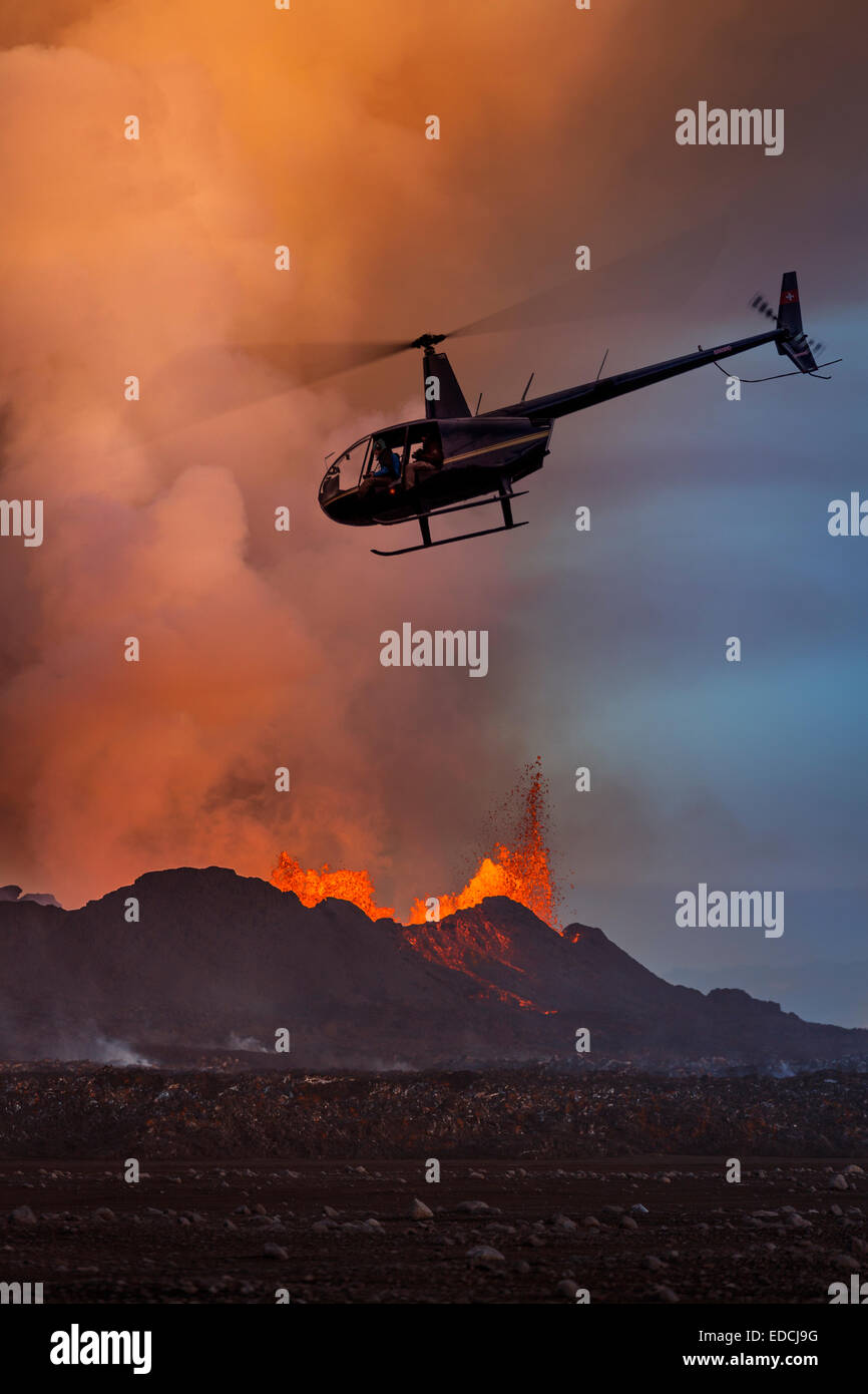 Helicopter flying close to lava and plumes, Holuhraun Fissure Eruption, Bardarbunga Volcano, Iceland - Stock Image