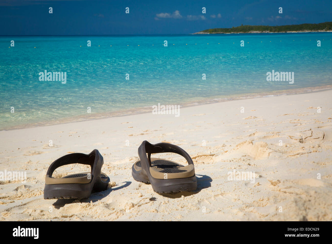 Flip flops on a sandy beach with turquoise water beyond, Halfmoon Cay, Bahamas - Stock Image