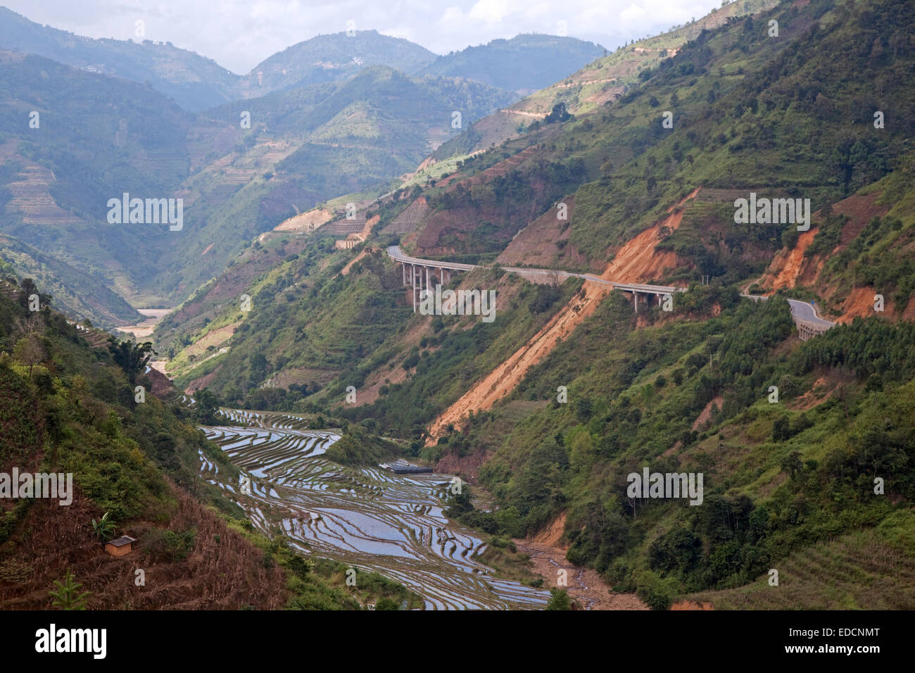 Chinese expressway and terraced rice paddies on hillside in the Yunnan Province, China - Stock Image