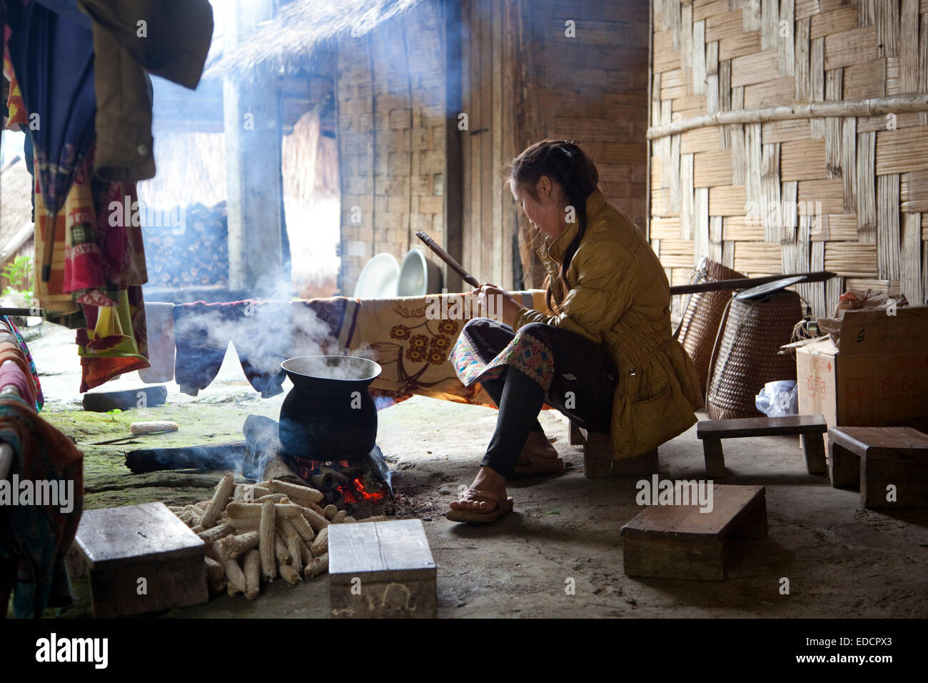 Lao woman cooking on an open fire in traditional bamboo house in rural village in Northern Laos - Stock Image