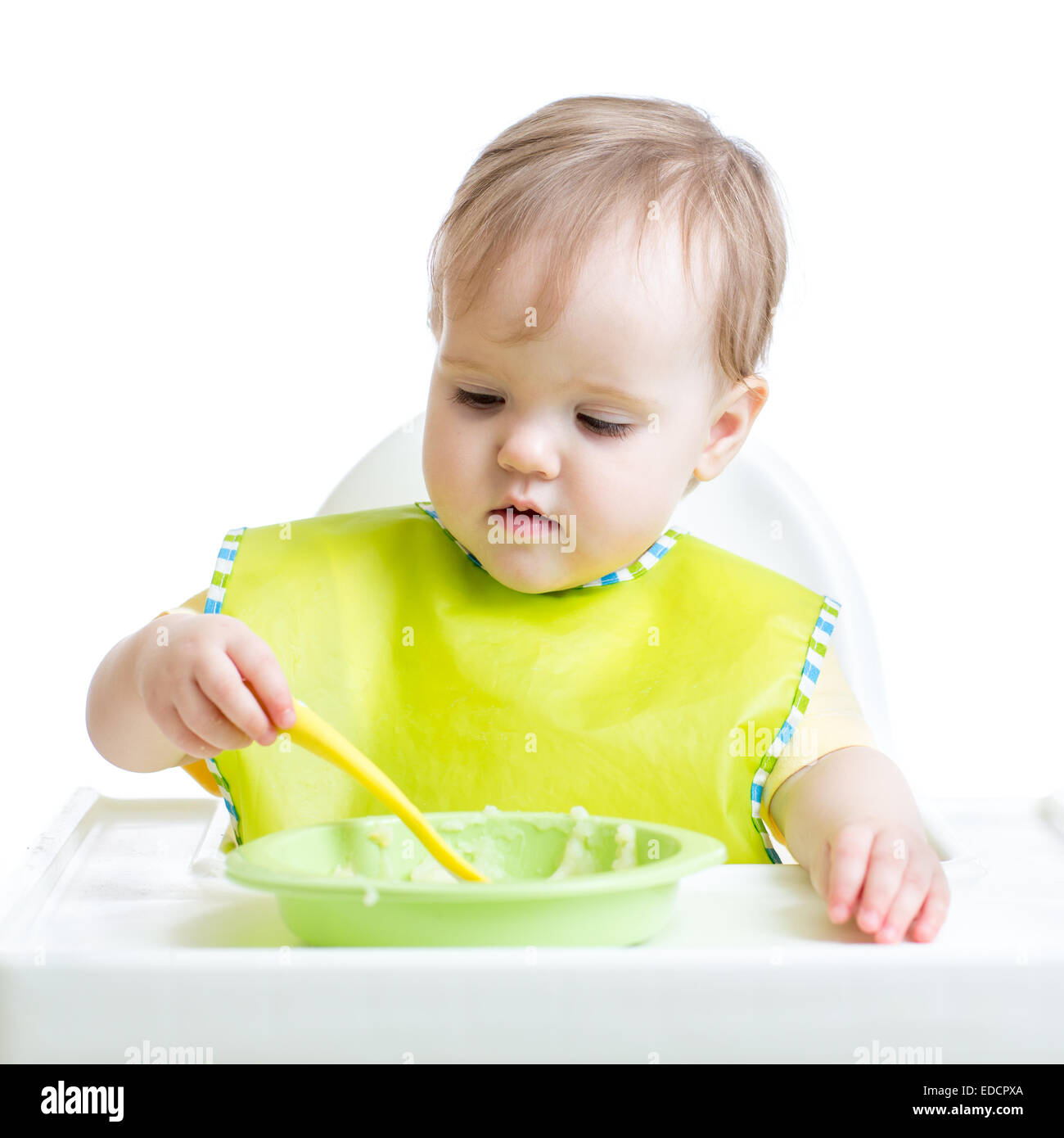 child girl eating singly with a spoon - Stock Image