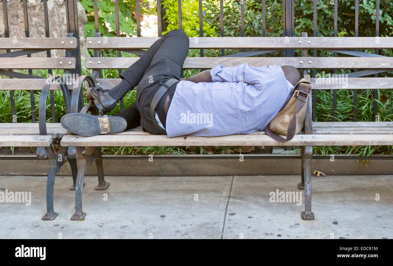 A man sleeping on a city park bench. - Stock Image