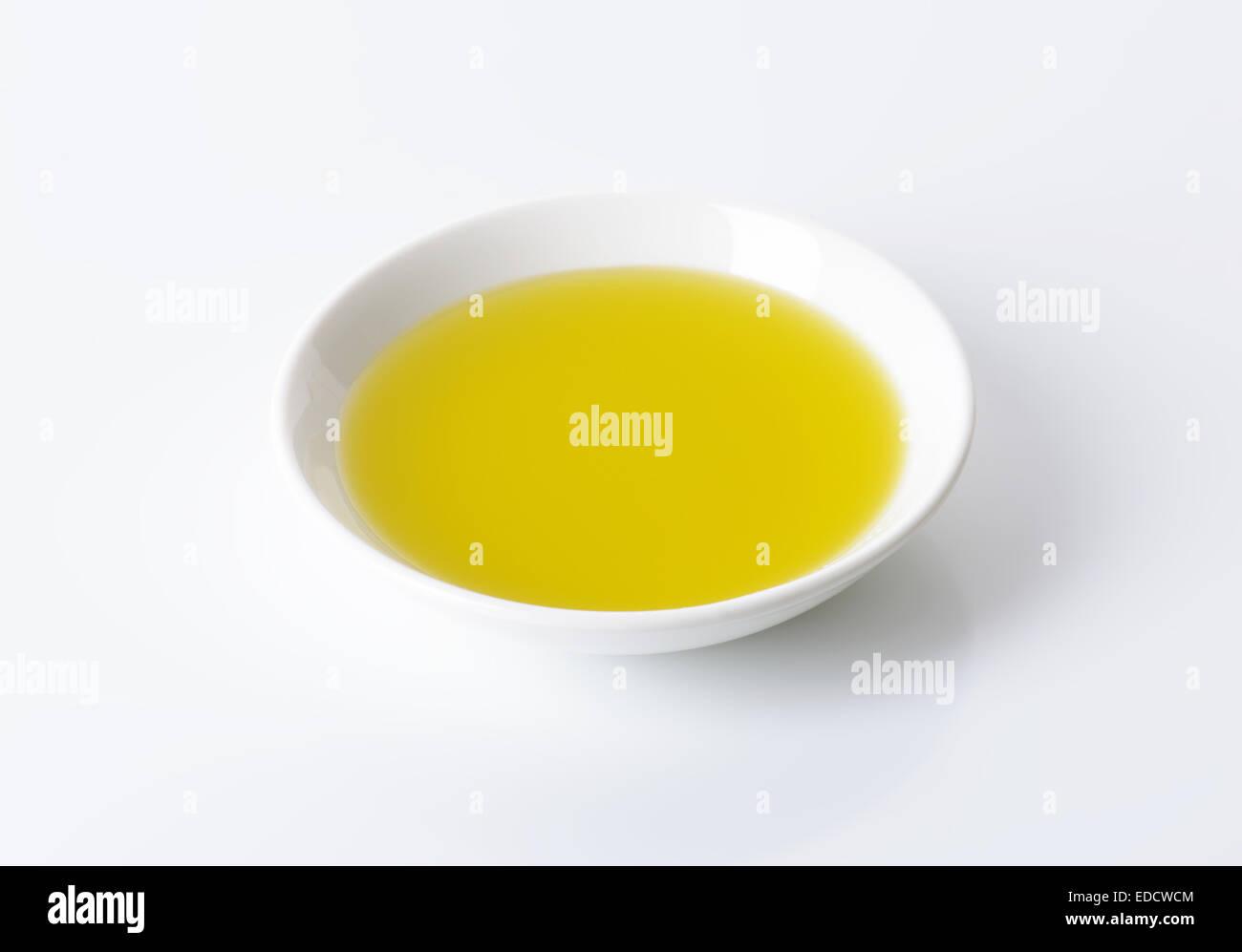 Olive oil in white porcelain bowl - Stock Image